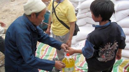 Boy distributing cooking oil to man