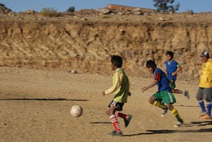 boys playing soccer on rustic soccer field