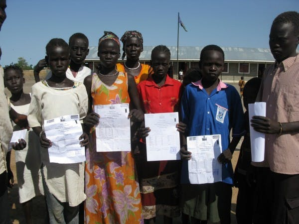 2010 students in Ulang displaying their report cards
