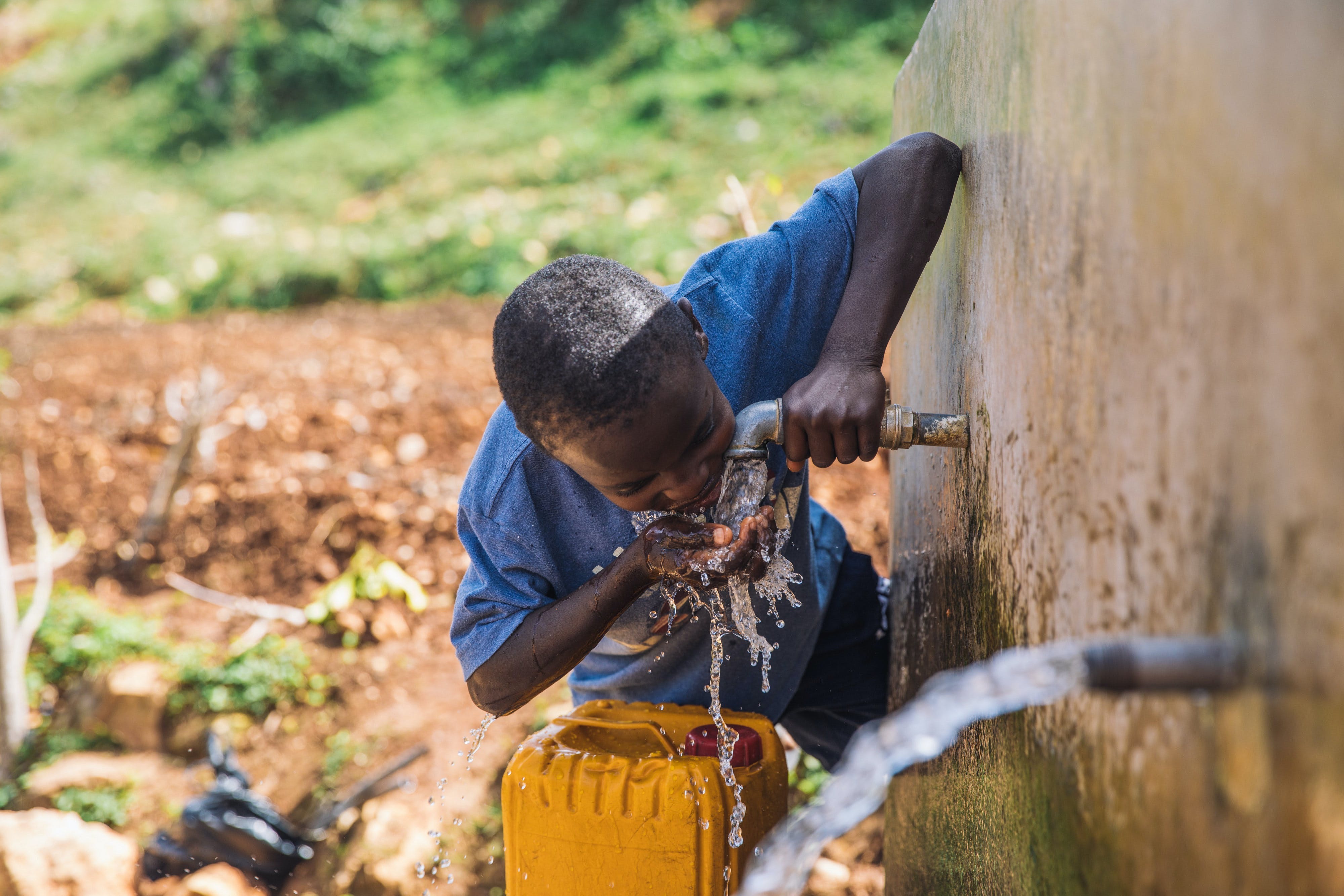 Boy drinks clean water from faucet in Haiti