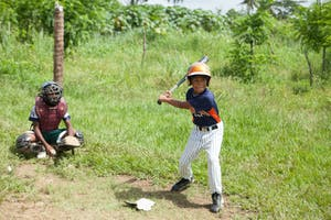 Children play baseball at a sports equipment distribution in the DR.