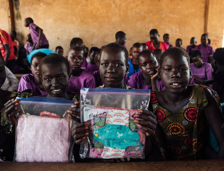 Girls in Uganda hold up women's hygiene kits