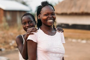 Two refugee women and friends in Uganda smile