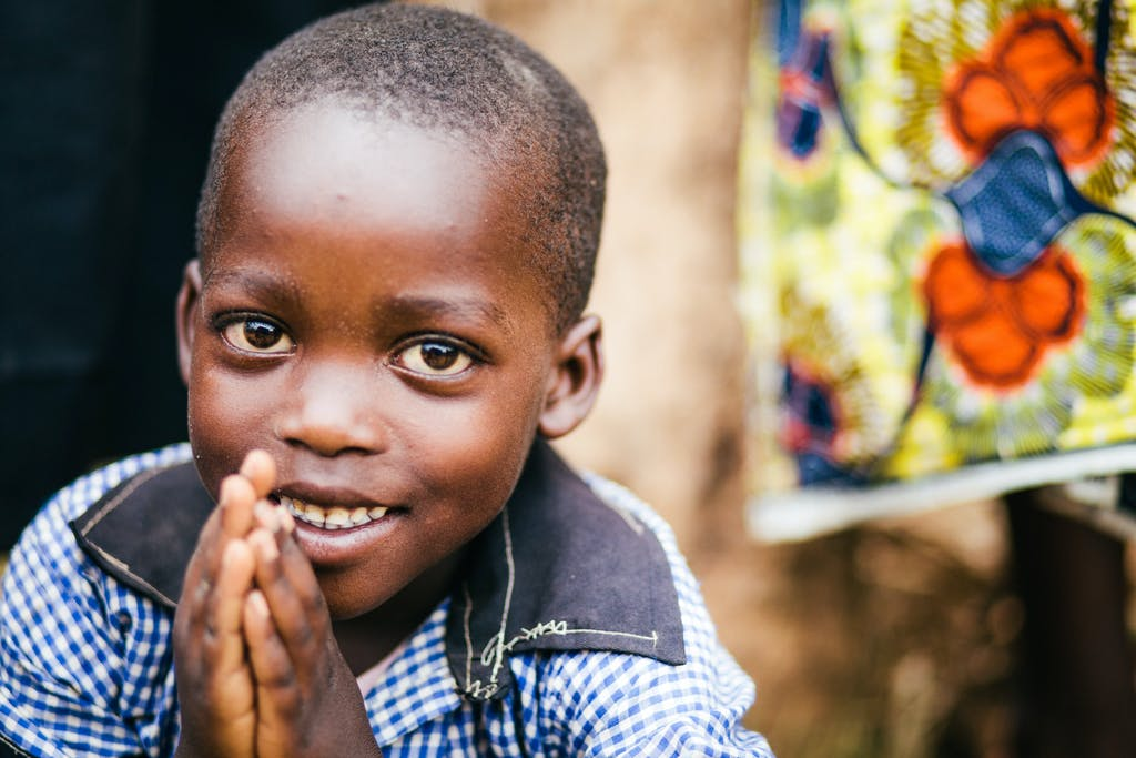 Young Rwandan boy in Food for the Hungry's work area folds his hands in prayer