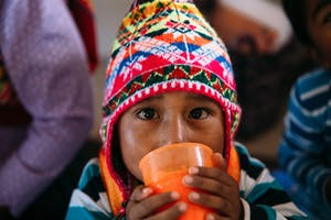 A little boy in the highlands of Bolivia wears a colorful chullo (hat) and drinks water from an orange cup.