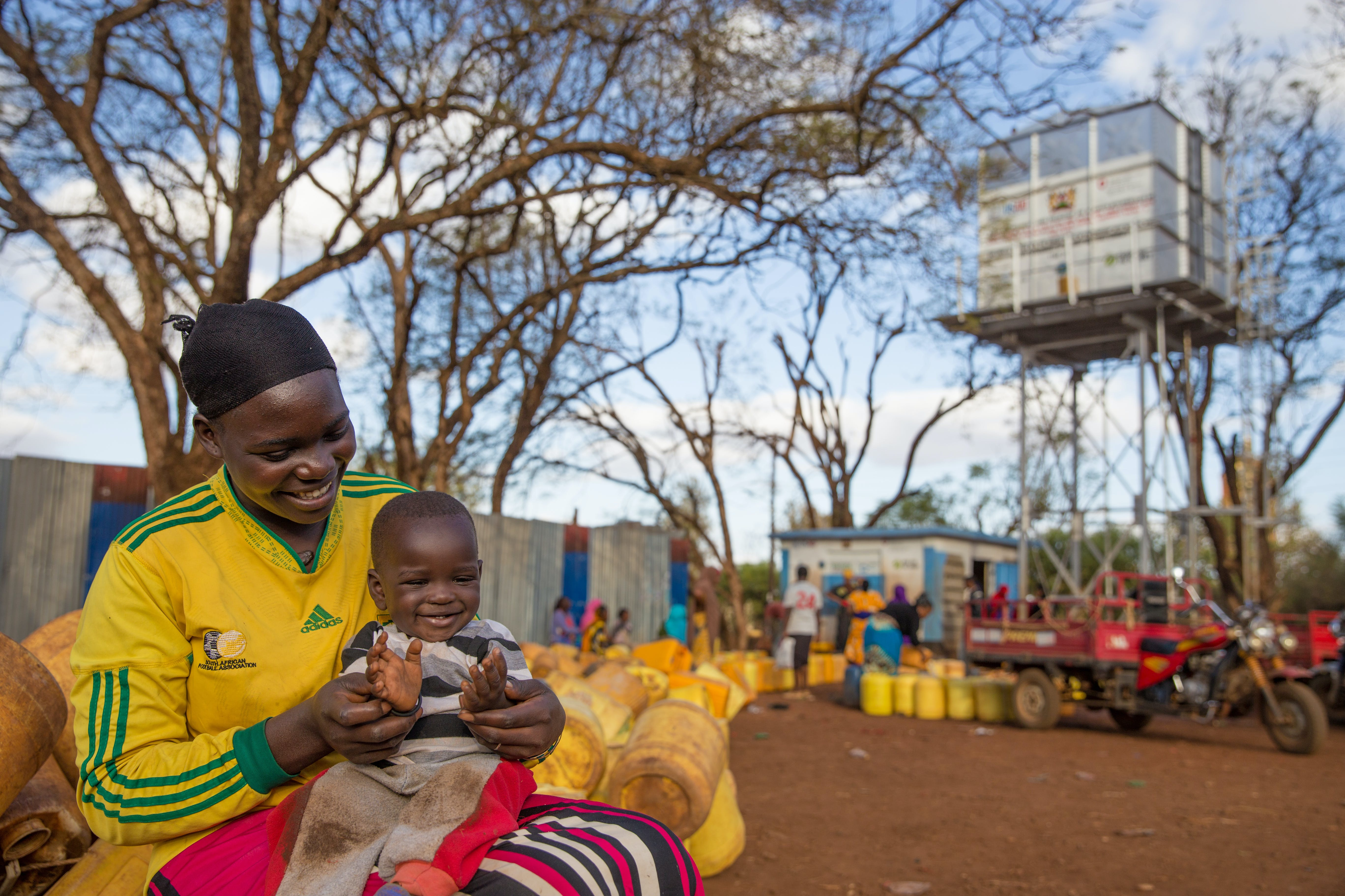 A woman holds her baby boy, in front of an innovative kiosk bring clean water in Kenya