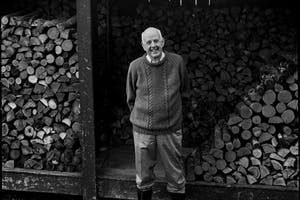 Wendell Berry stands in front of a storehouse of logs.