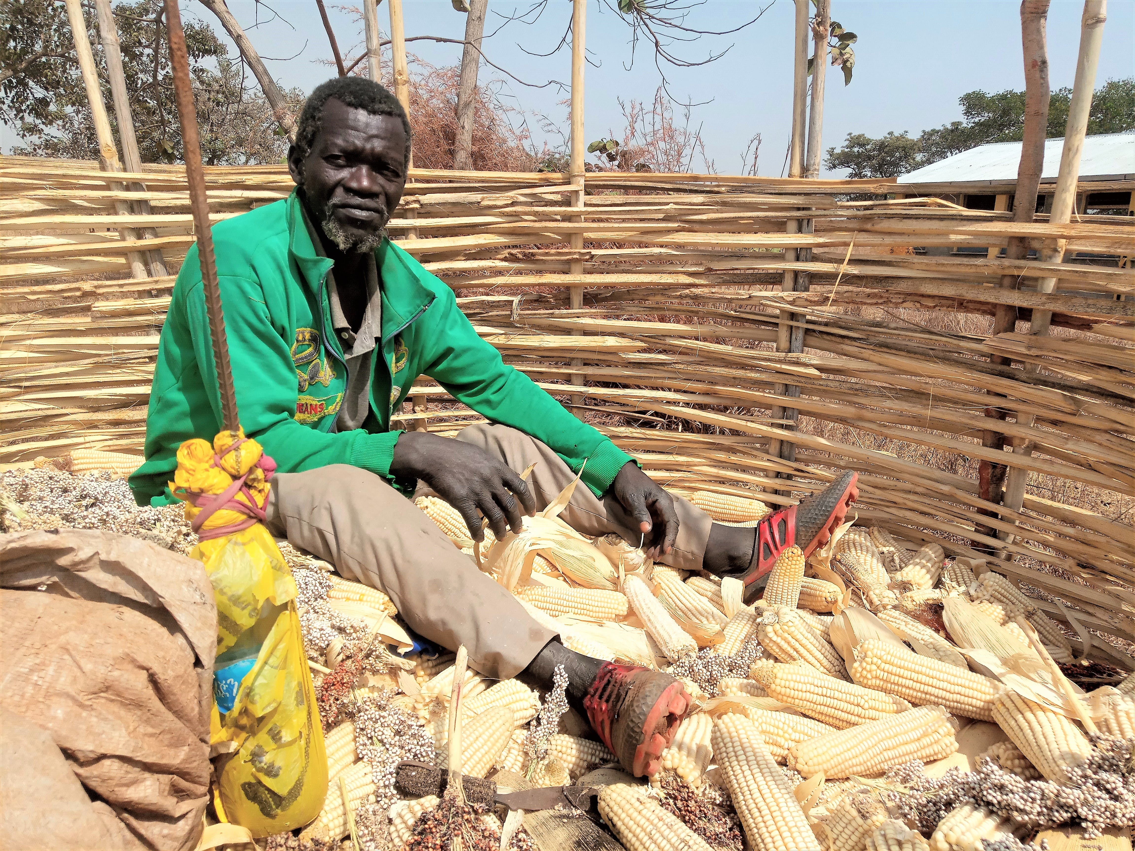 Abdela sorts maize in his grain store.