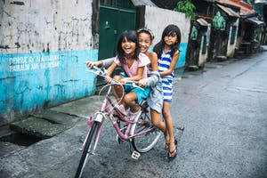Girls riding a bike in the Philippines