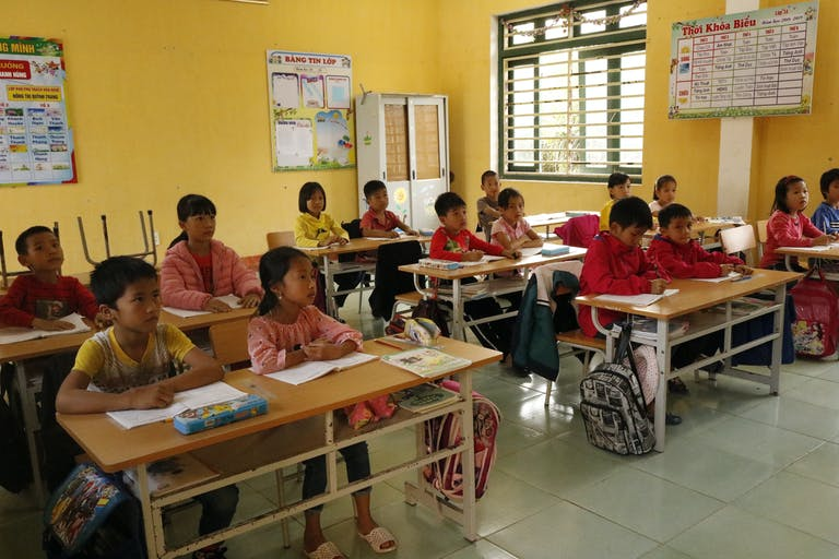 Elementary school children in Lien Minh, Vietnam pay attention to their teacher and sit at their school desks in a classroom with yellow walls