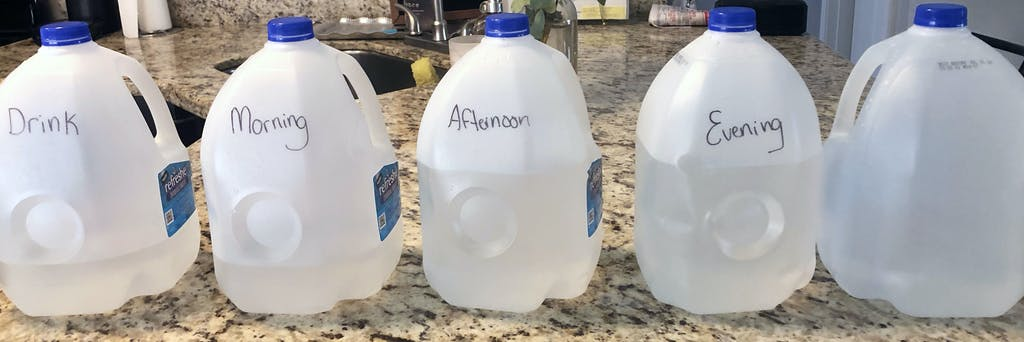 5 gallon jugs with different levels of water in them