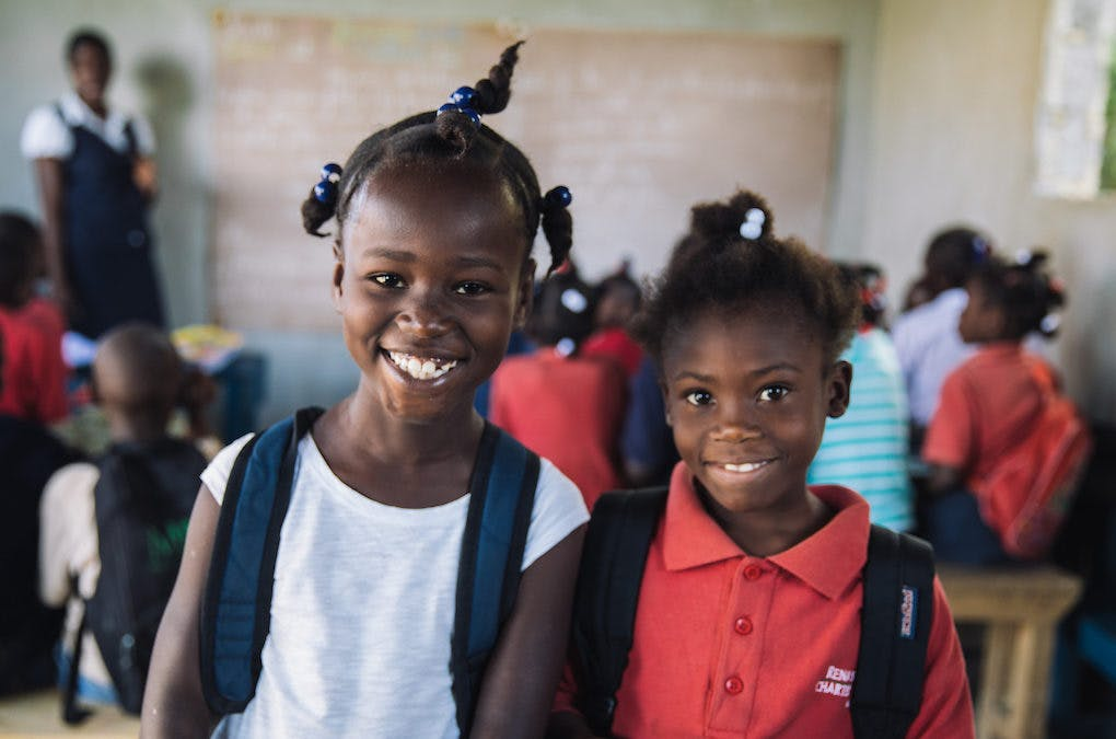 Two girls in the community of Francois in Haiti proudly wear their backpacks in school