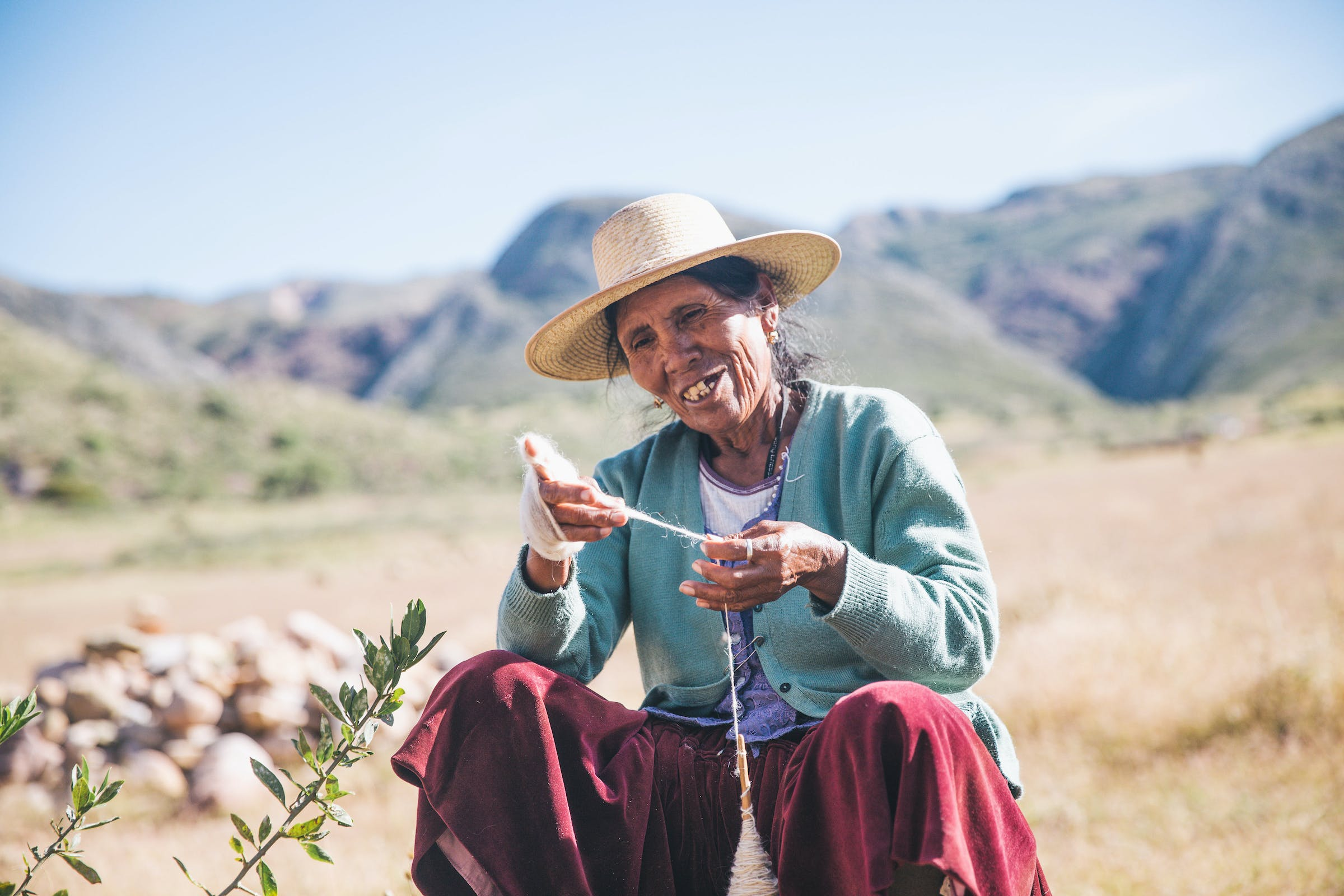 Elderly Boliivan woman in hat making yarn from wool