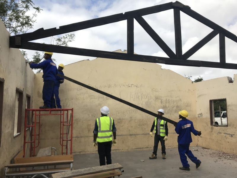 Men installing beams to hold a new tin roof on cement block school building