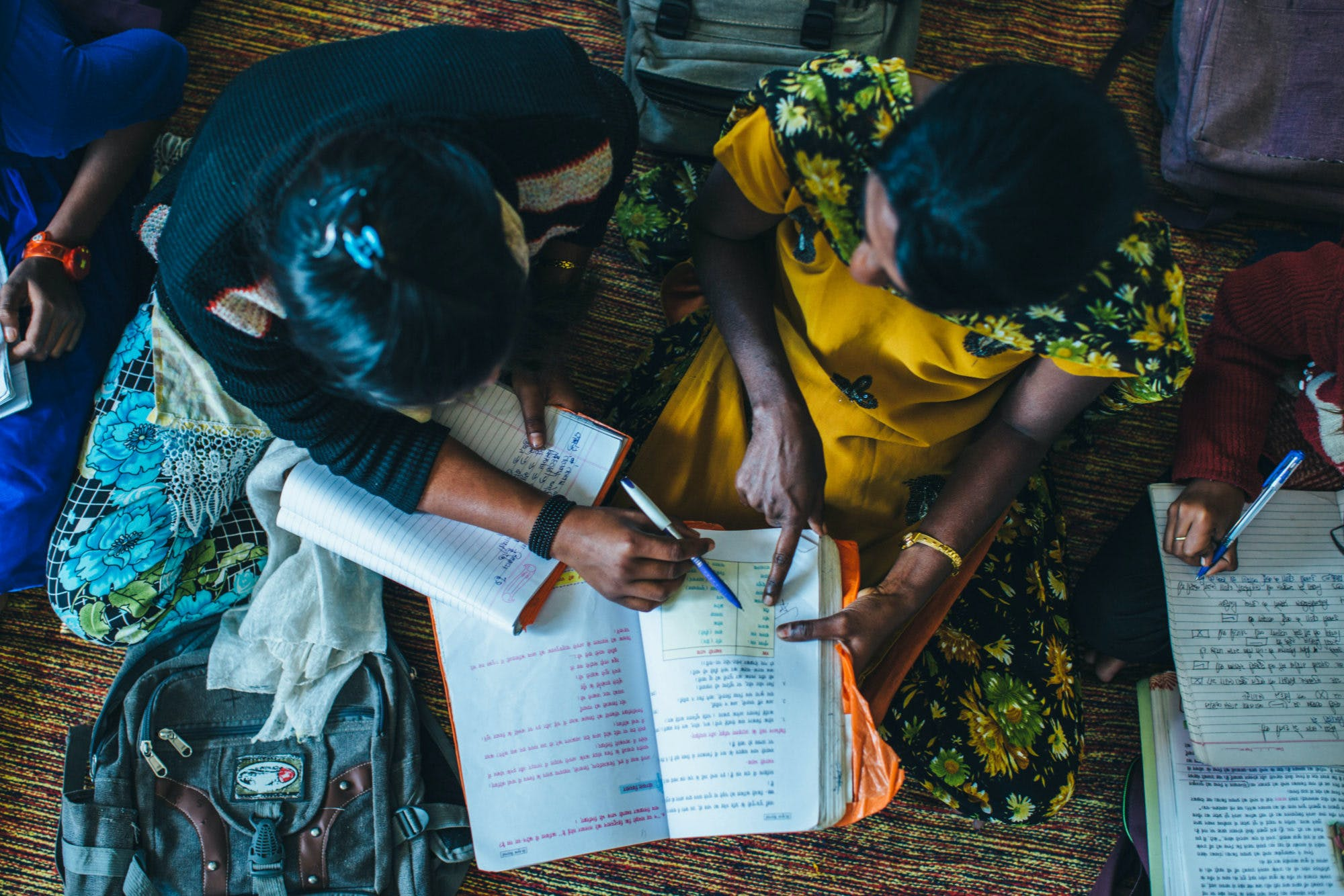 Aerial shot of two girls in developing community of India hovering over a textbook and reading together