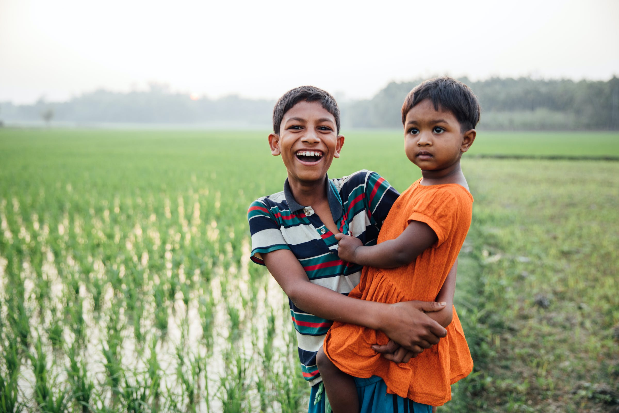 A young Rohingya boy carries his sister in the backdrop of a green field