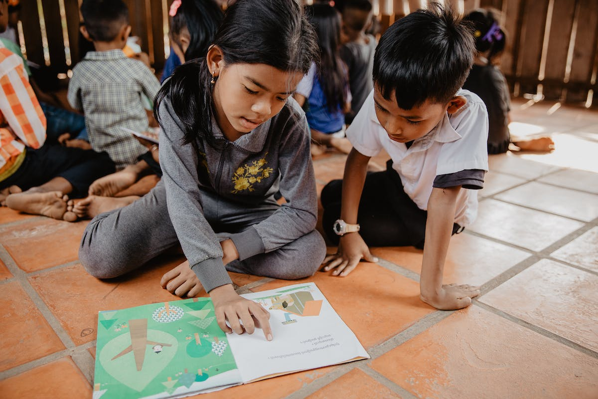 Two kids in Cambodia read a picture book