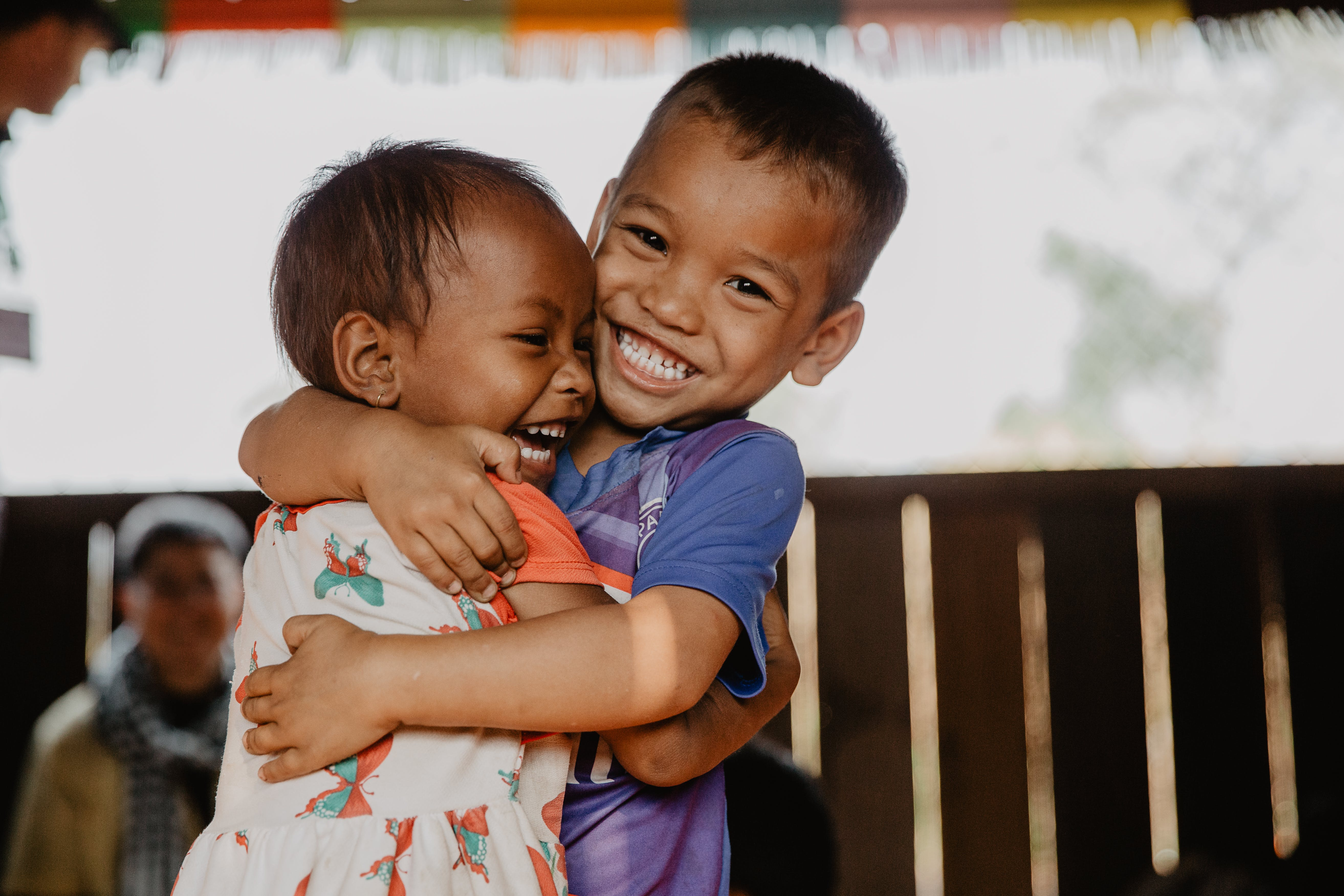 Two kids in Cambodia embrace in a warm hug