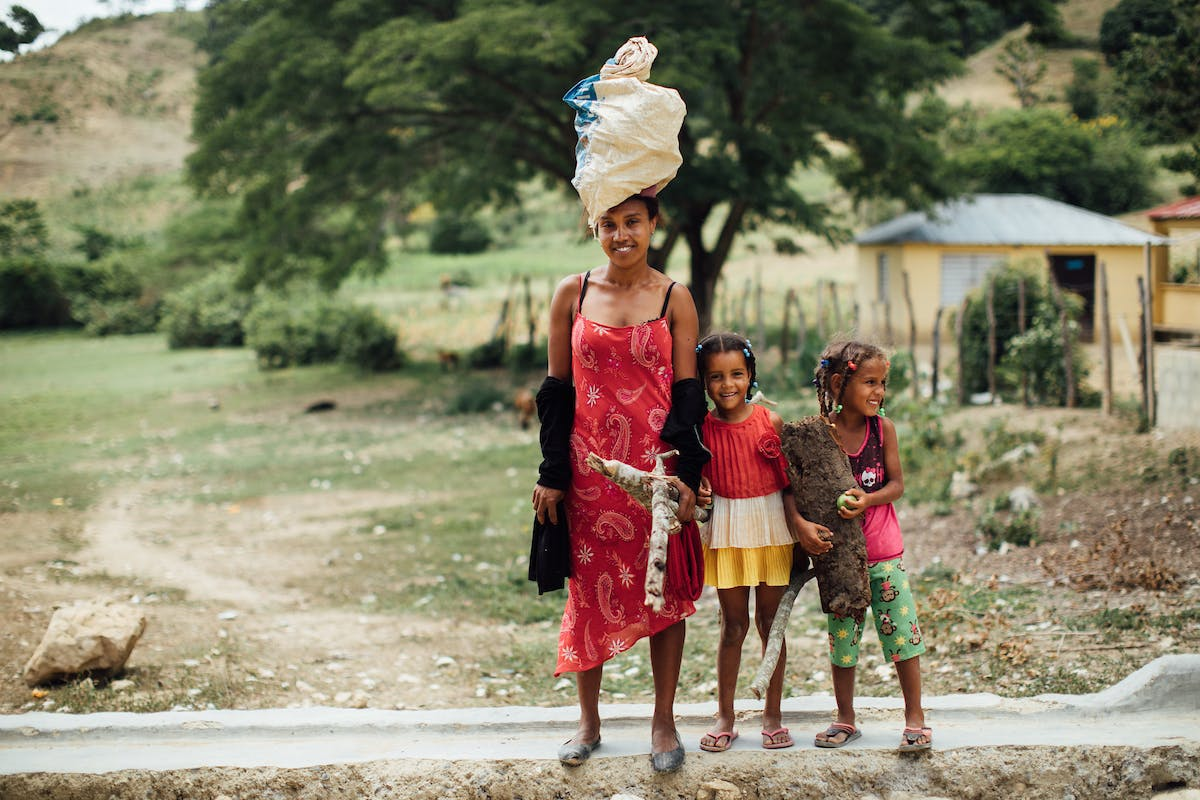 A woman with a bag on her head, and two children next to her in the Dominican Republic