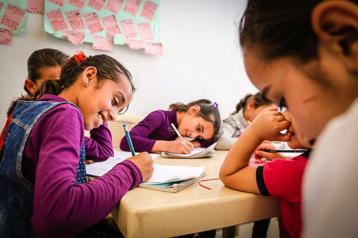 A group of Syrian refugee girls do classwork at a desk in Lebanon, as part of a FH/MERATH program