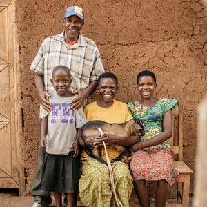 A family in Burundi holding a goat