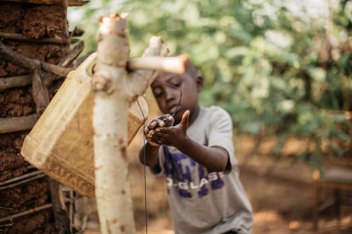 """Little boy washes his hands in Burundi from a """"tippy tap"""" with a jerrycan."""
