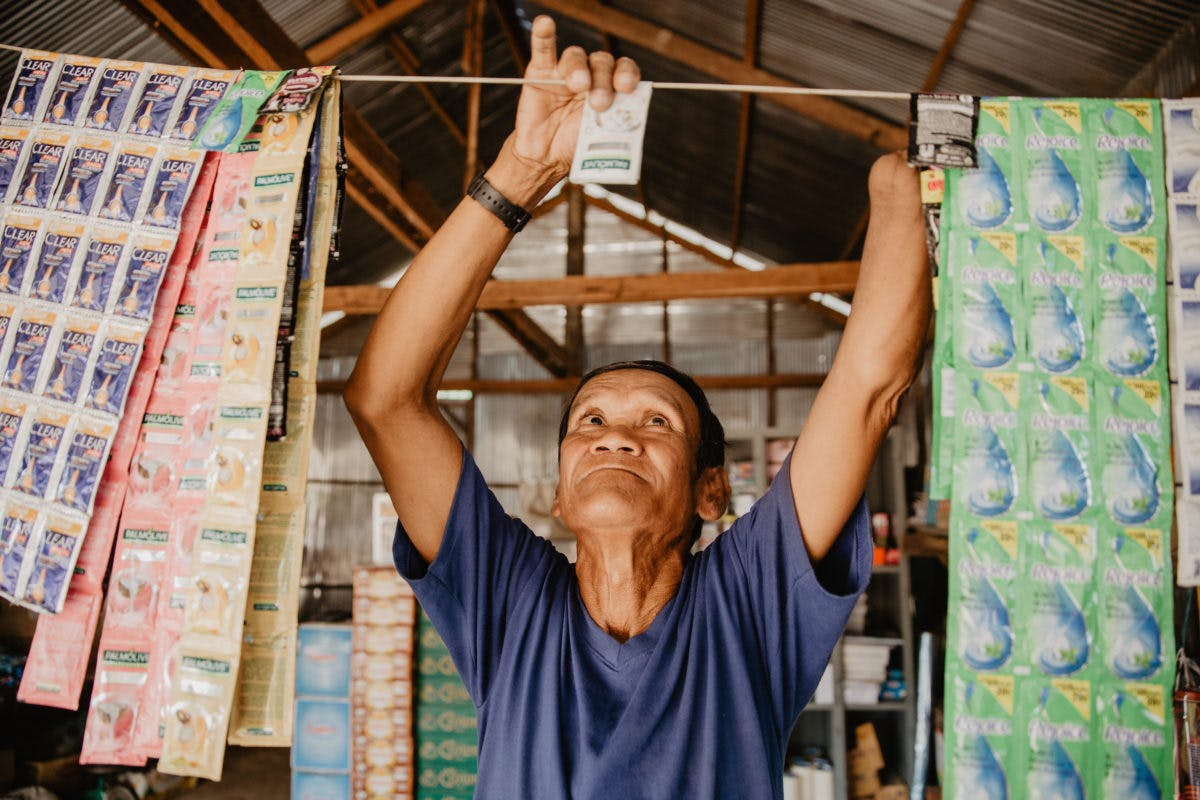 Disabled man in Cambodia grocery co-op hands up an item in the store with his one hand