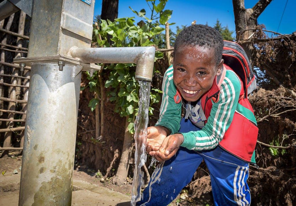 boy-at-the-water-hand-pump
