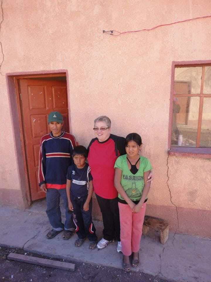 Marcella, an FH child sponsor and staff member, poses for a photo with her sponsored child Raul and his family in Bolivia.