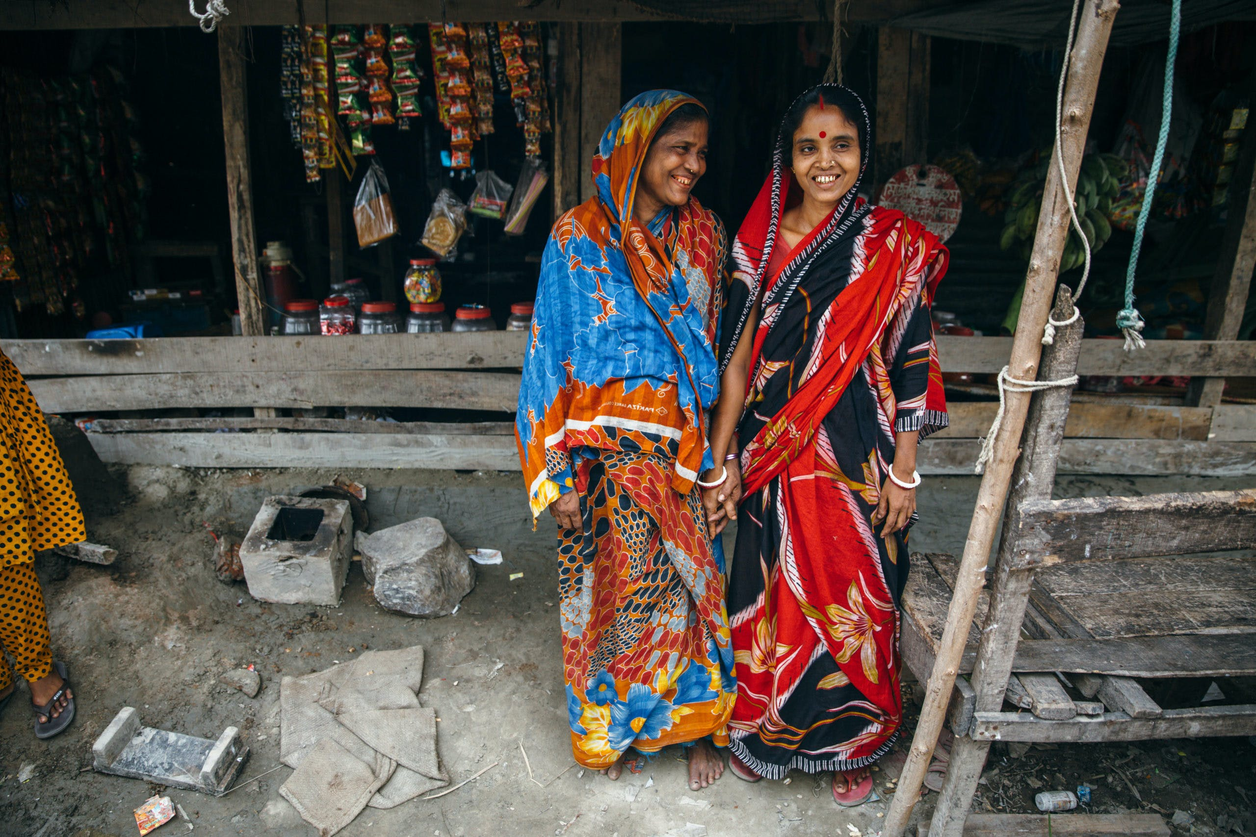 Two women from Bangladesh smiling and holding hands