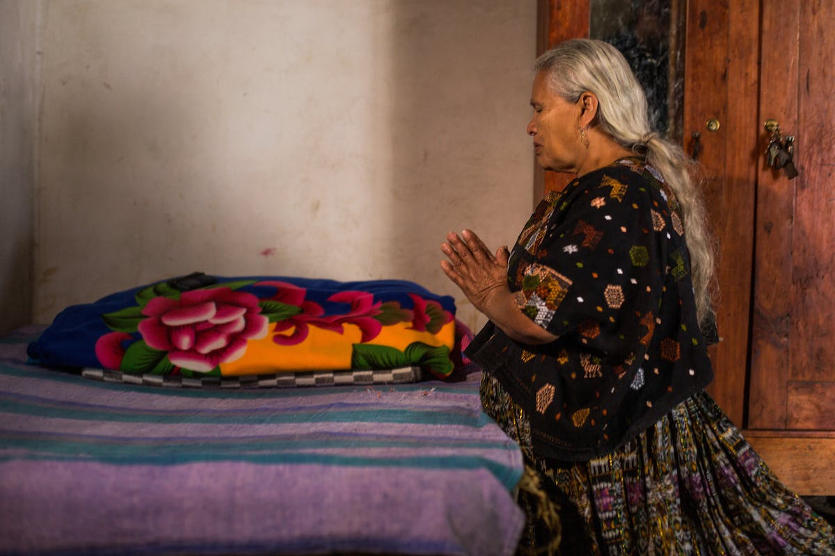 Guatemalan elderly woman prays and kneels by her bed