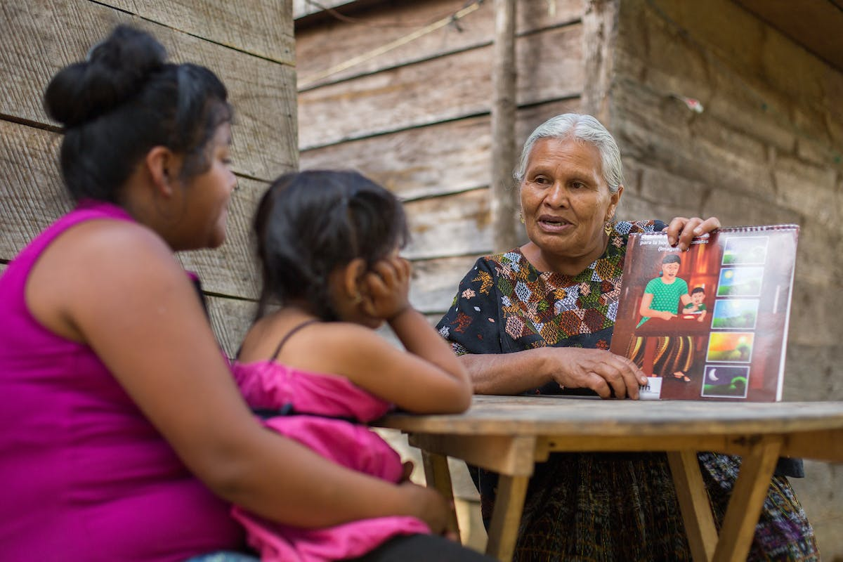 woman in traditional guatemalan dress teaching hygiene to mother and child