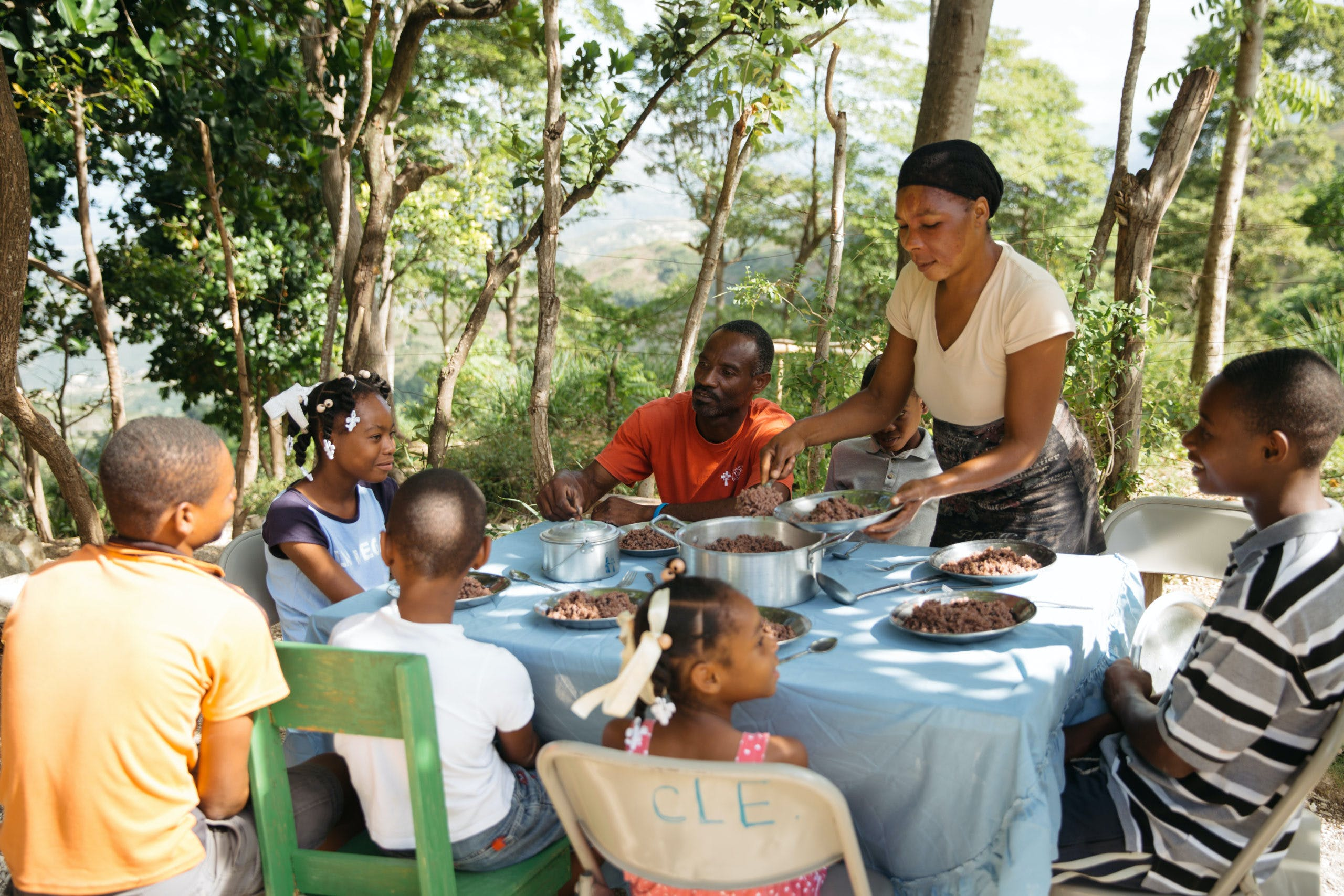 A mother serves beans to her family around a big table outside