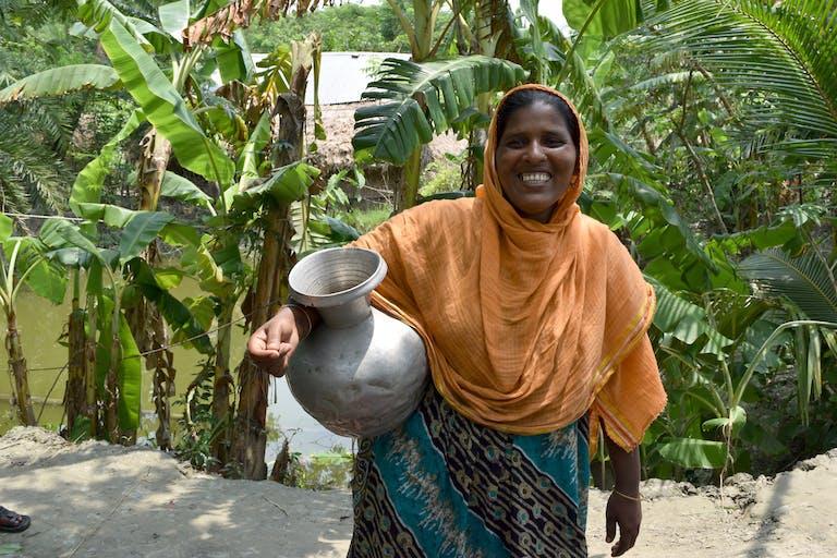 Woman in orange sari in Bangladesh holding a metal jug smiling