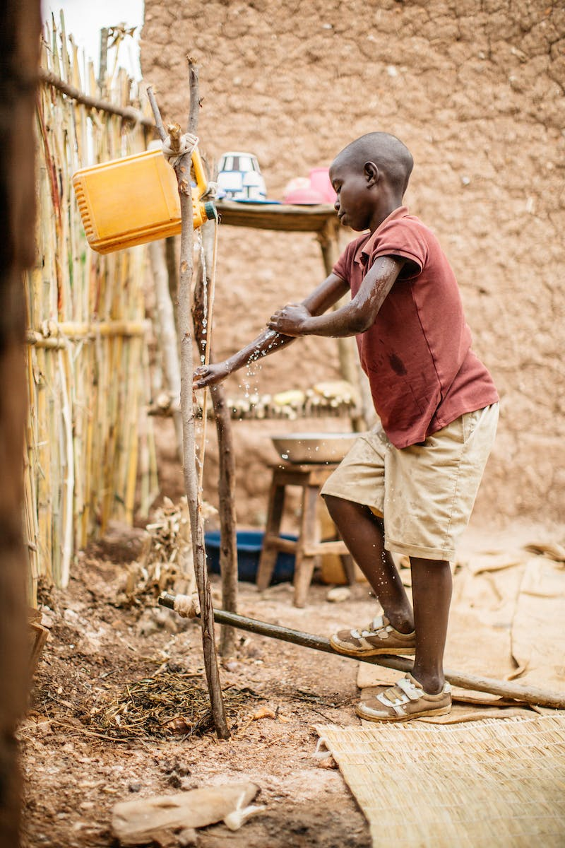 Burundian boy washing hands with tippy tap