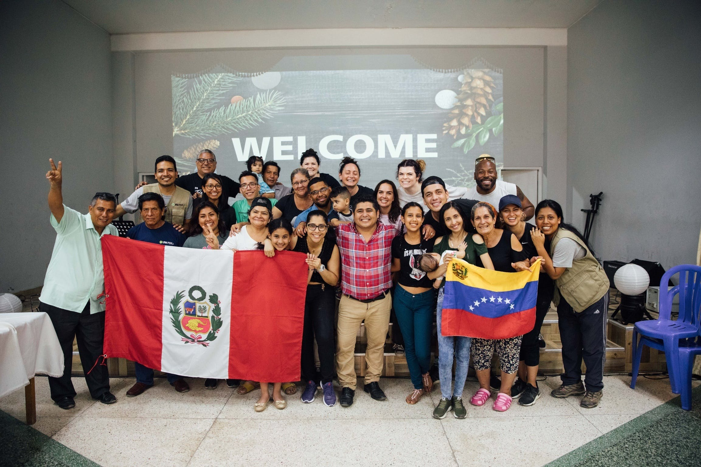 Anthony Evans visits Peru and meets Venezuelan refugees, seen in a group shot here holding up the Peru and Venezuela flags