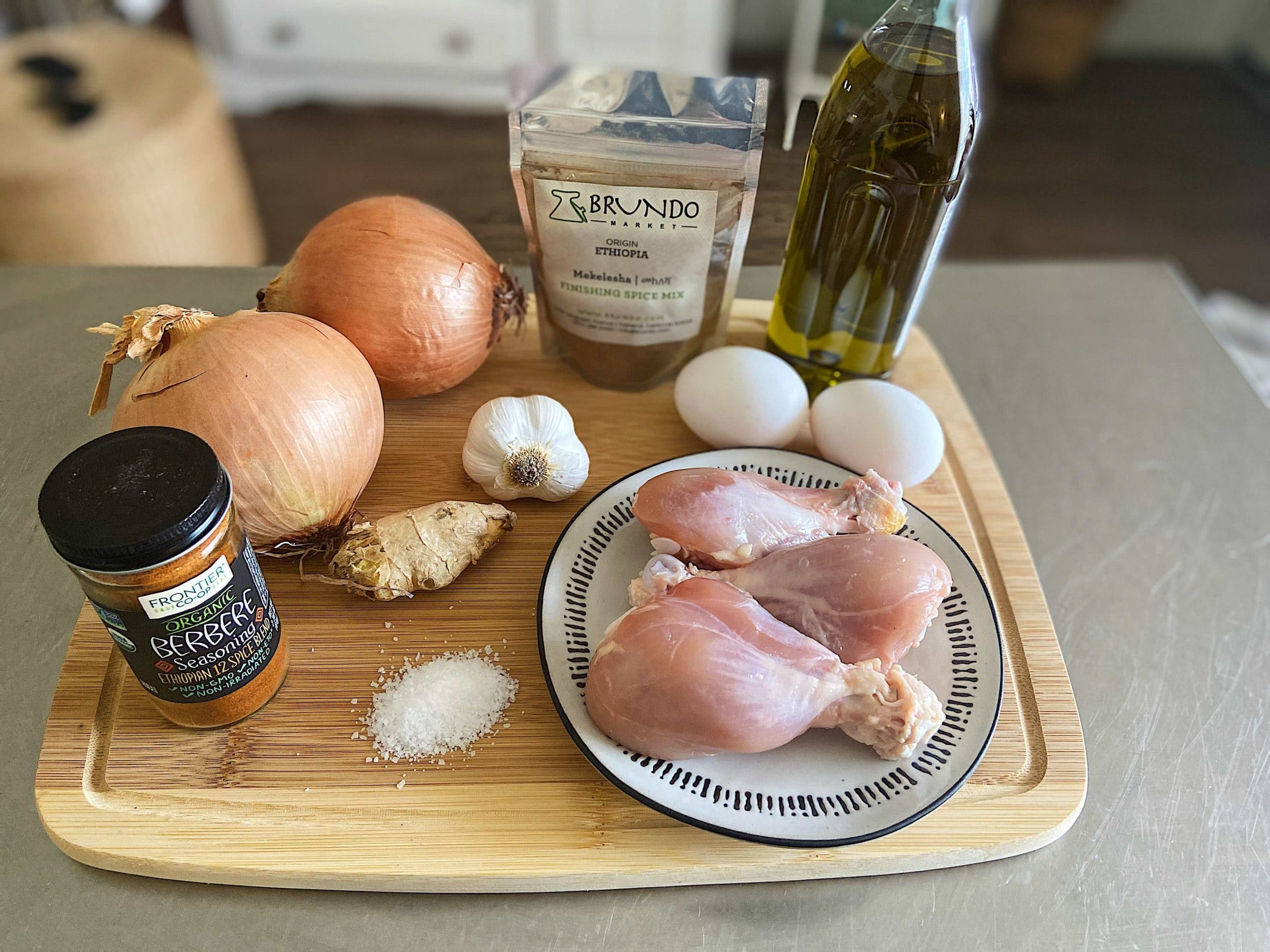 ingredients needed to make doro wat on top of a cutting board