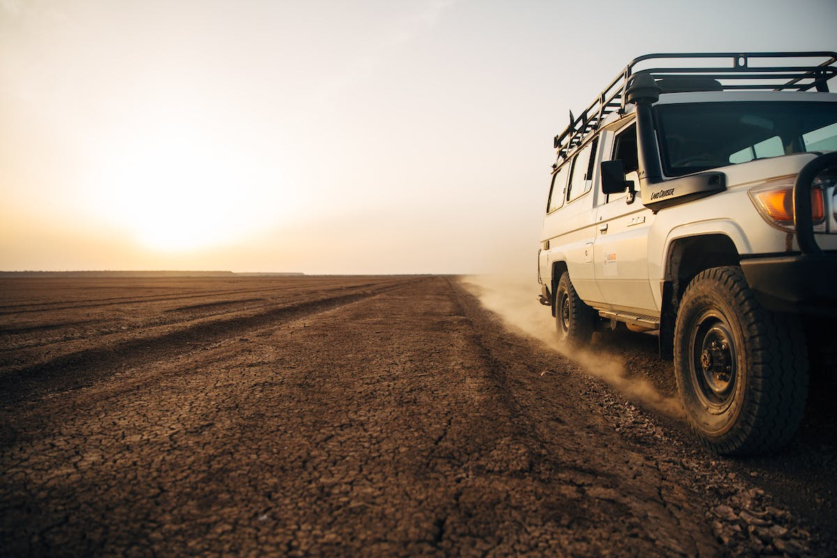 Jeep driving on dusty road with horizon in the background
