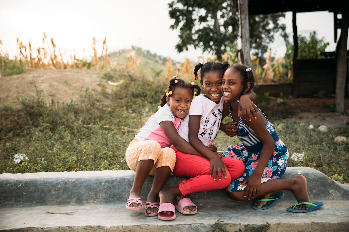 Cute photo of girls sitting on a log smiling and hugging in the Dominican Republic