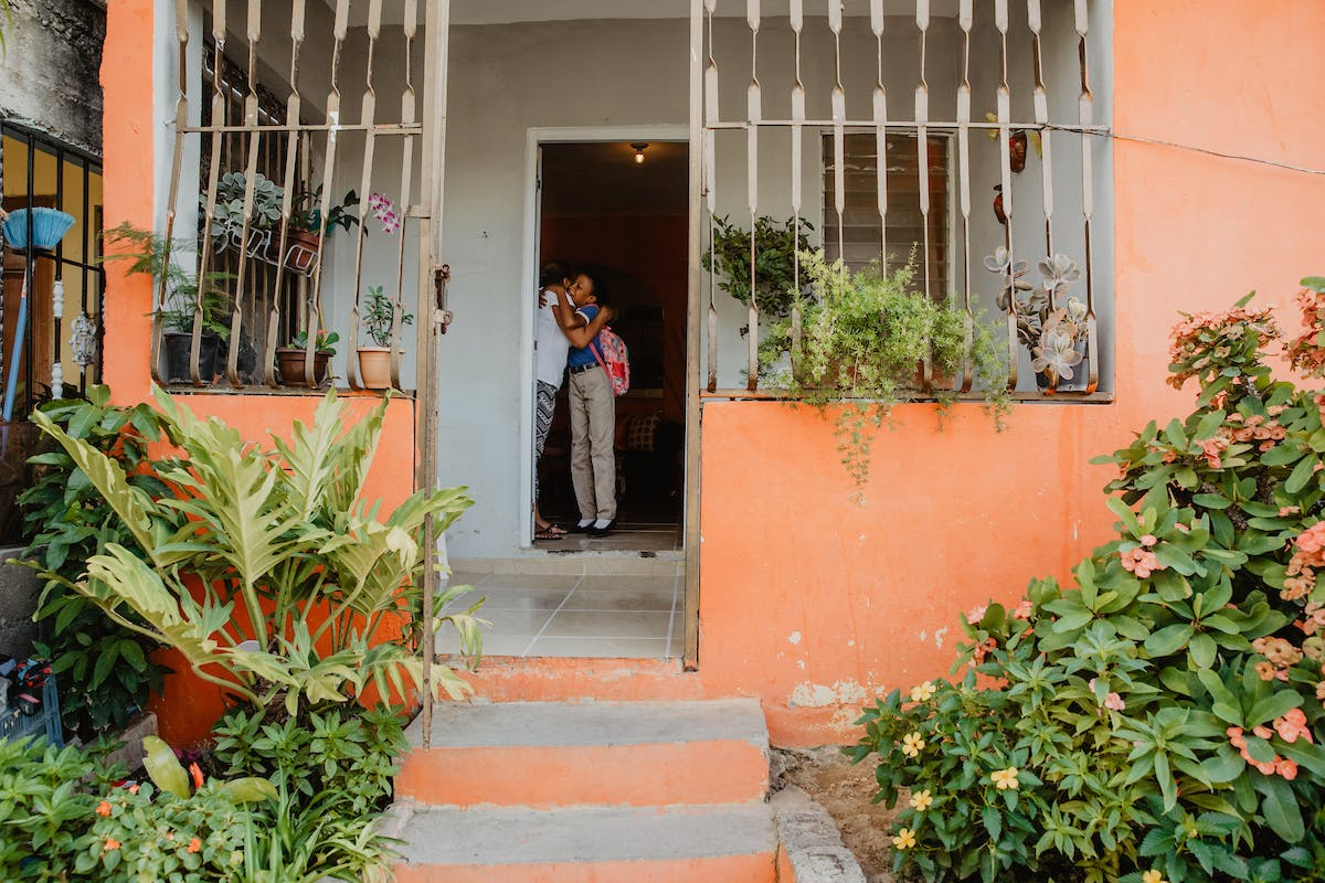 Mother hugs daughter with a backpack going to school in Dominican Republic, showing orange exterior of house