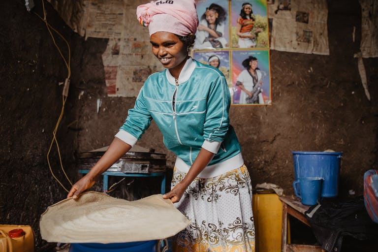Sintayehu, who was an orphan, bakes injera bread for her business in Ethiopia.