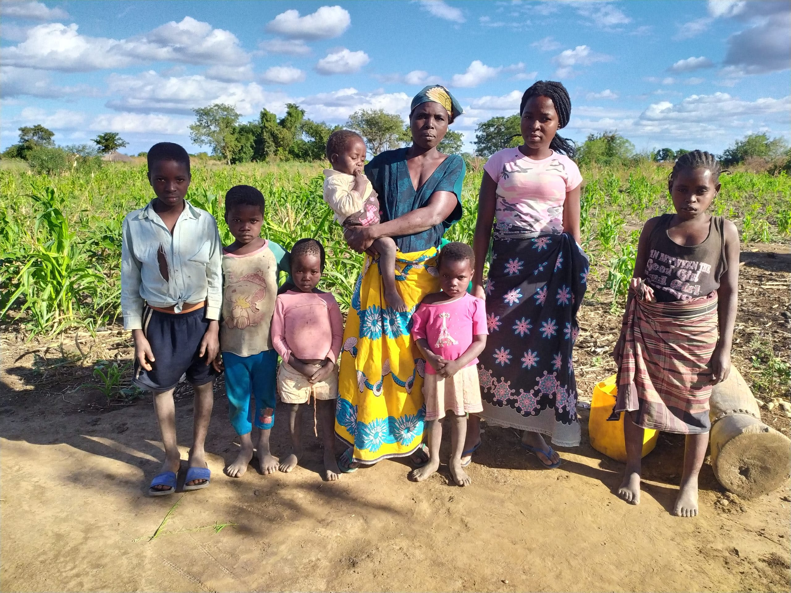 Rosita and her children pose for a photo in front of their fields.