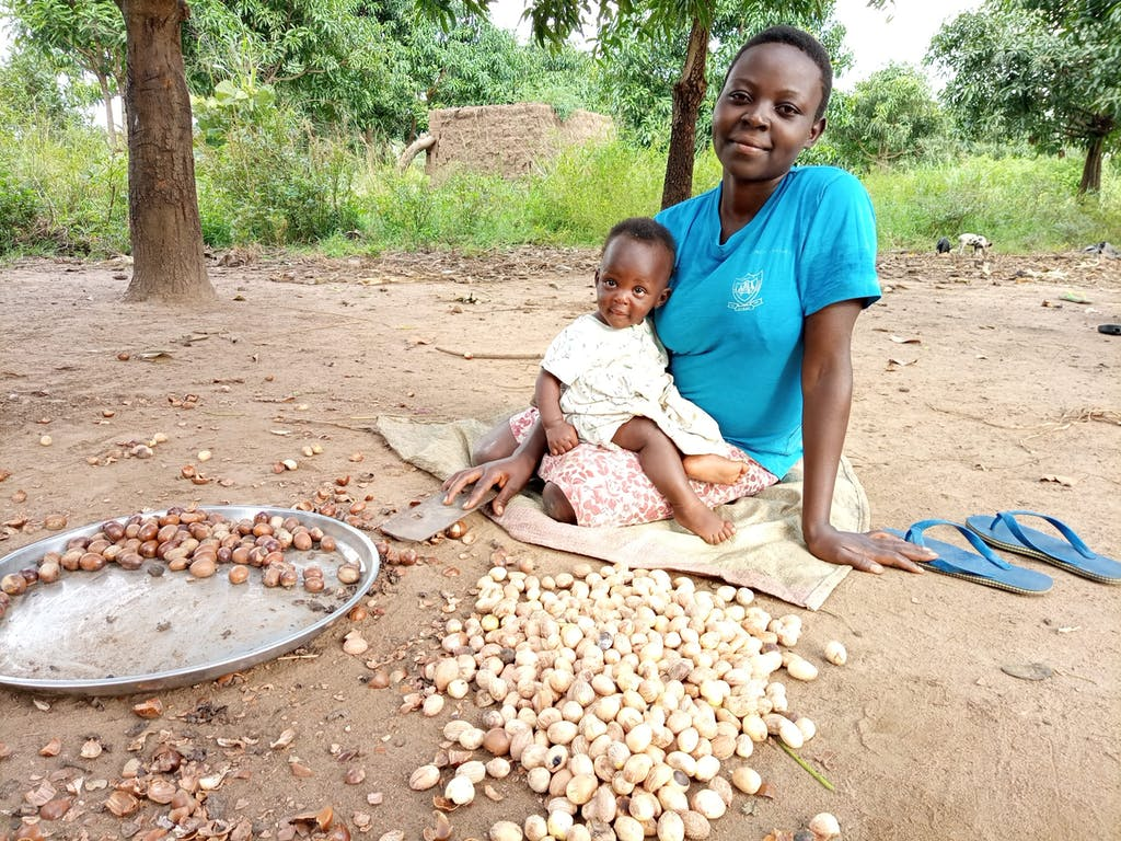 woman with young baby sitting on the ground with shea nuts