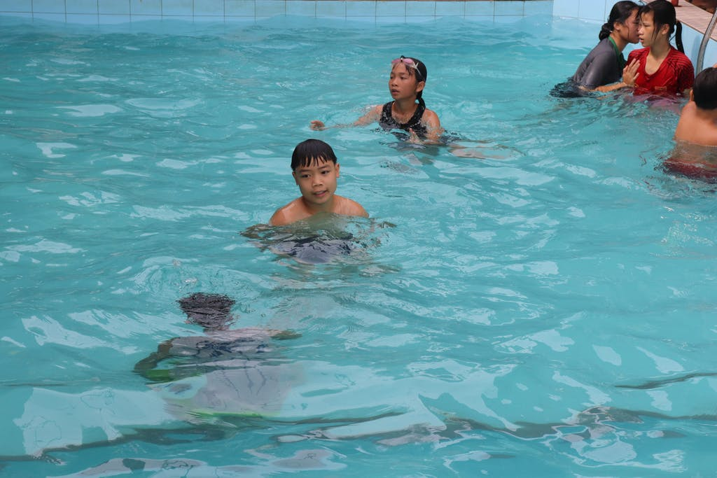 Children in swimming pool with boy looking at camera