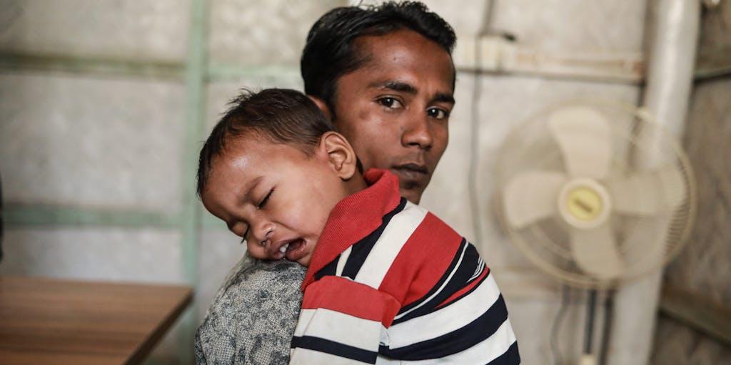 Rohingya Man holding small toddler.