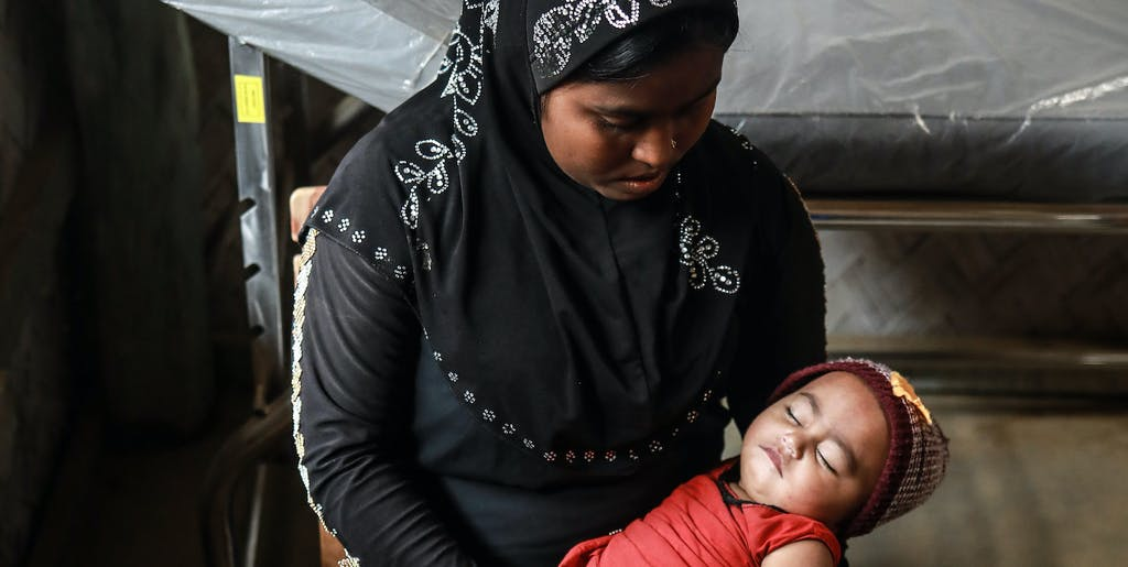 Rohingya mother holding her baby.