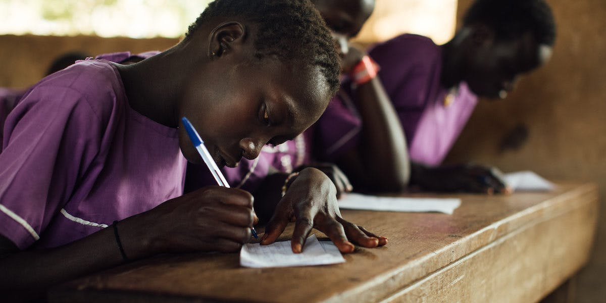 Child sitting at a desk writing a letter.