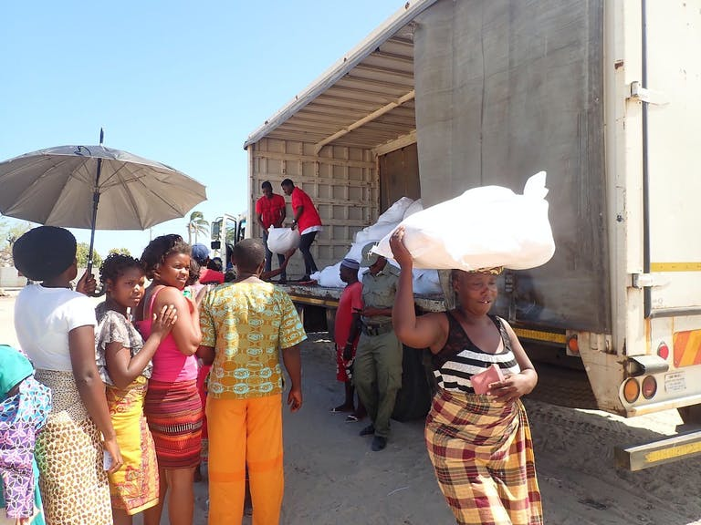 people receiving sacks of food from truck