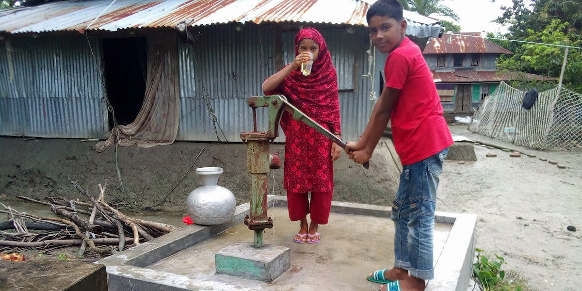 Children in Bangladesh using tube well to get clean water.