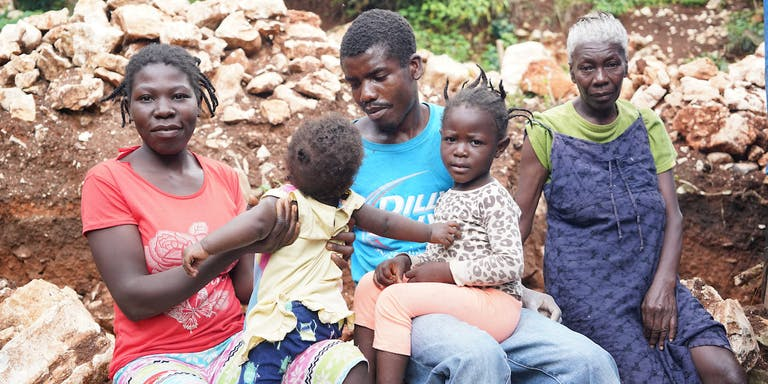 Family with small children from Haiti sitting together.